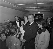 Vice President Lyndon Johnson, with Jackie Kennedy at his side, is sworn in as president immediately after the assassination of John F. Kennedy in 1963. He took the oath of office as the 36th President, aboard the presidential jet, Air Force One, before Sarah T. Hughes, U.S. District Judge which also returned Kennedy's body to Washington, D.C. Johnson's presidency began with a flurry of legislative activity.